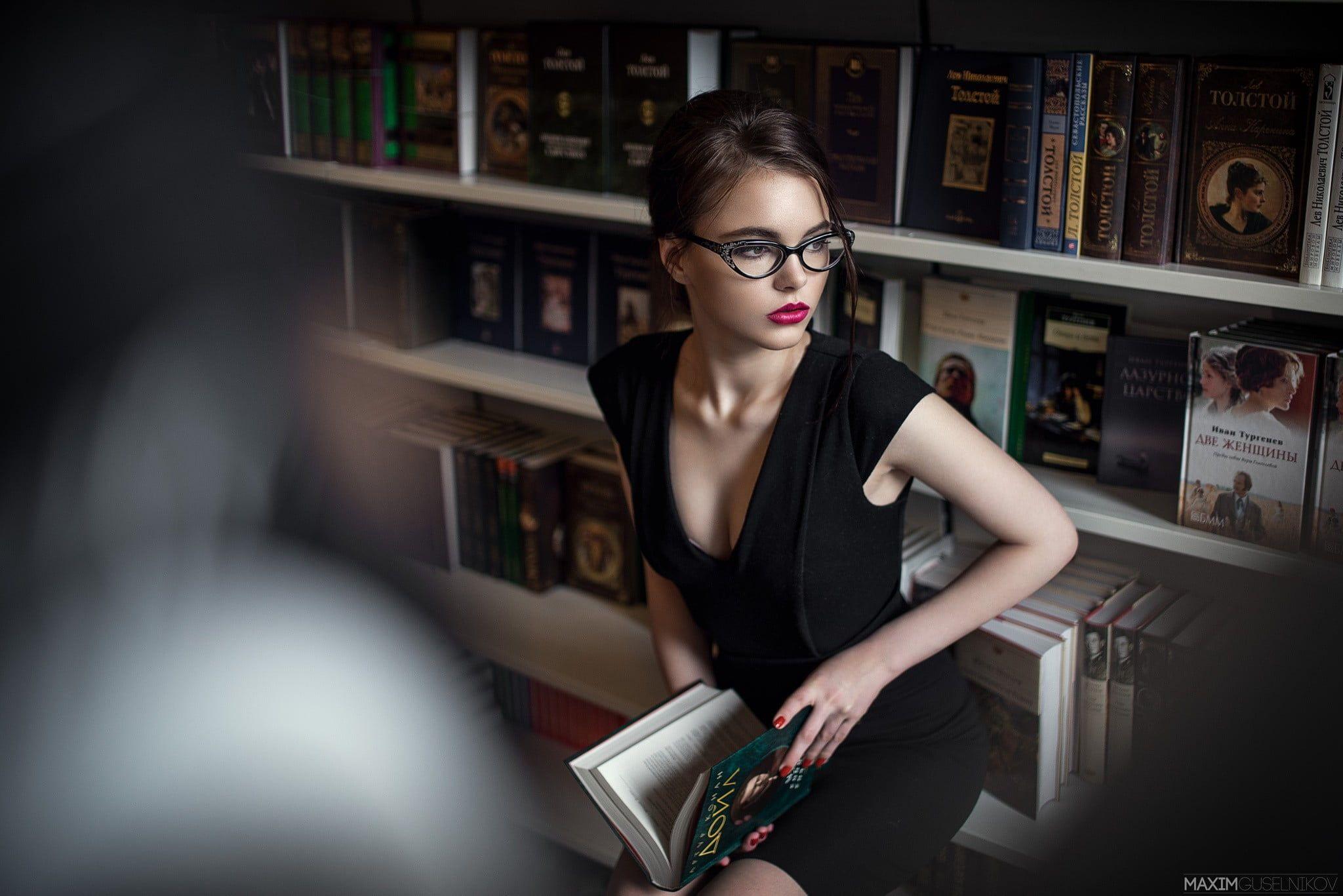womens black capsleeved dress woman wearing black body con capsleeved dress sitting inside library women with glasses red lipstick Oktyabrina Maximova black dress red nai...