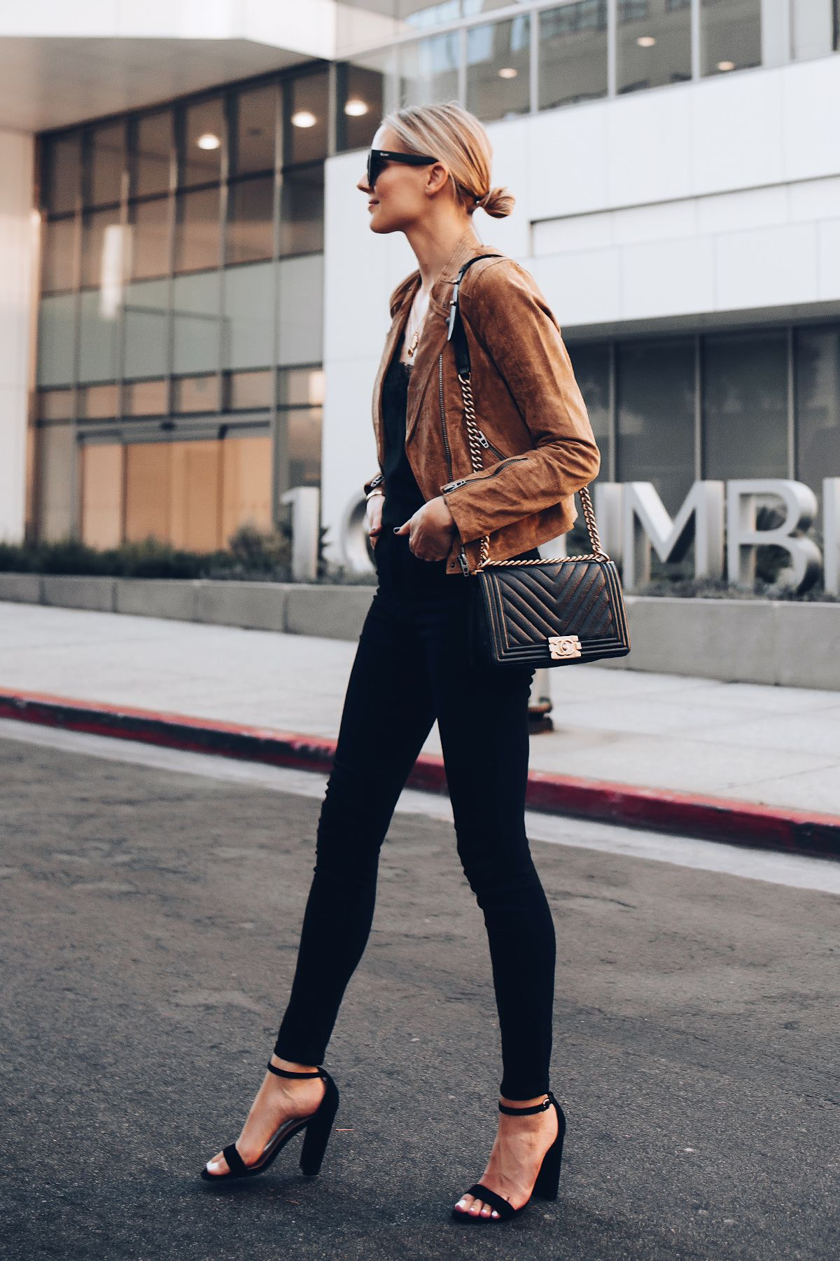ea23fa4a227 Blonde Woman Wearing Blanknyc Tan Suede Moto Jacket Black Lace Cami  Everlane Black Skinny Jeans Outfit Black Ankle Strap Heeled Sandals Chanel  Black Boy Bag ...