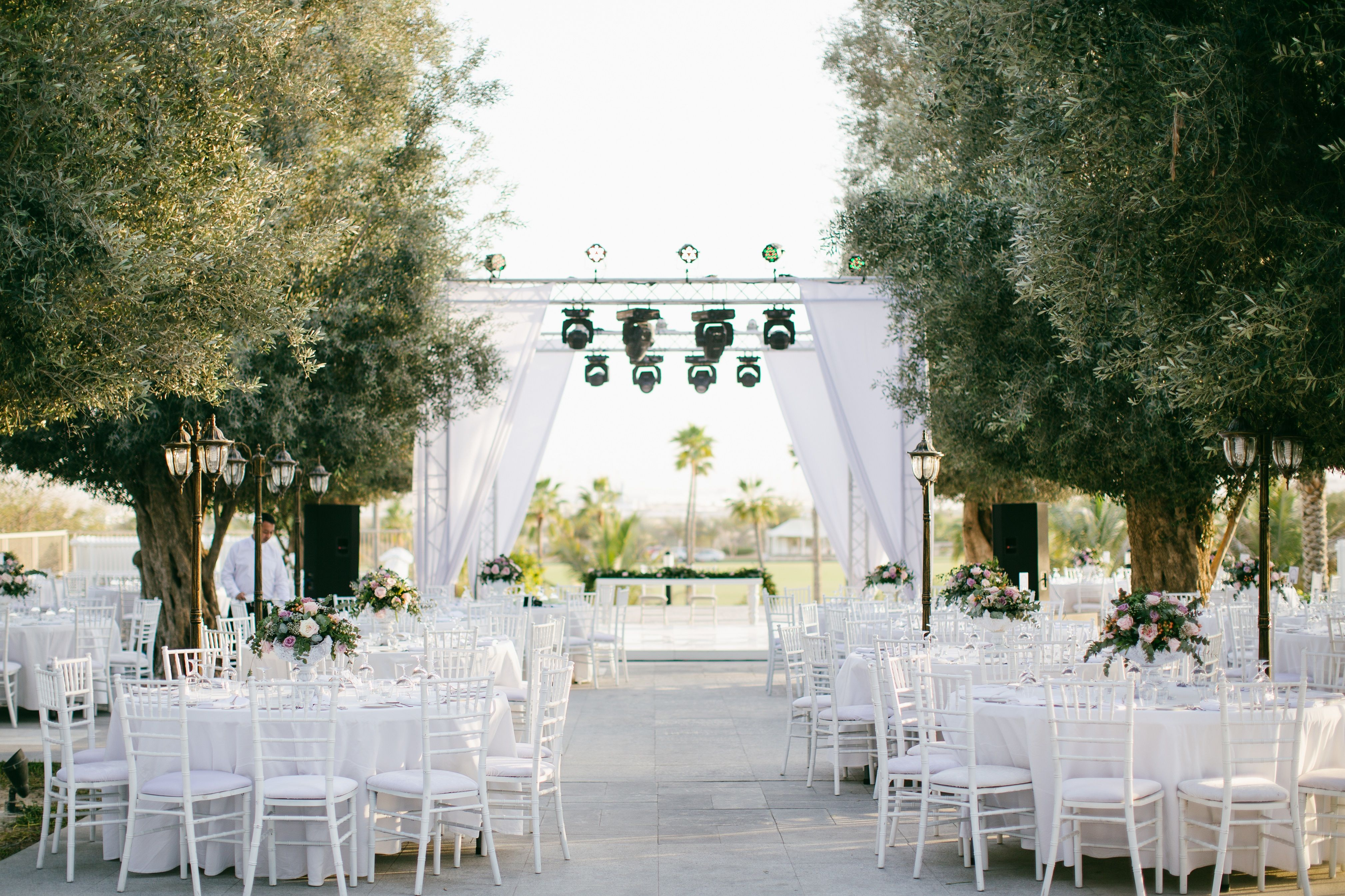 Outdoor olive garden wedding setting in Dubai. White round tables ...