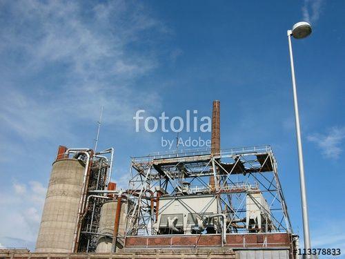 Alte Fabrikanlage mit Silo und Schornstein und mit einer modernen Straßenbeleuchtung im Vordergrund am Hafen in Münster in Westfalen