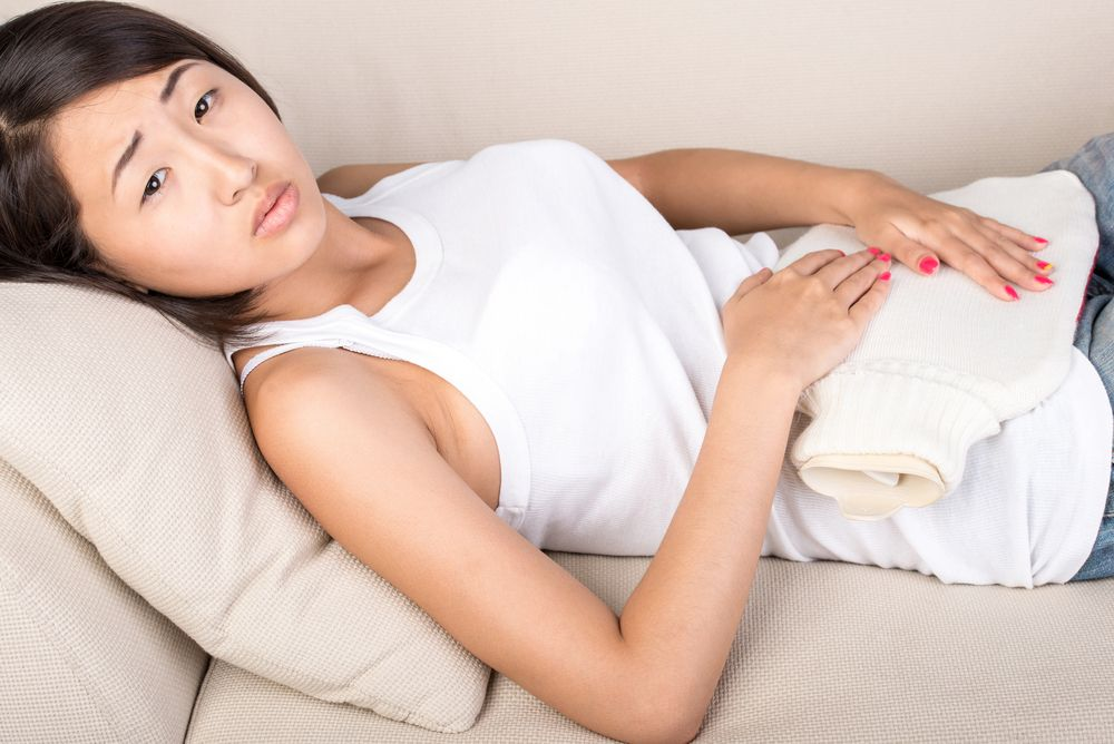 asian young woman is holding a heating pad on the abdomen ...