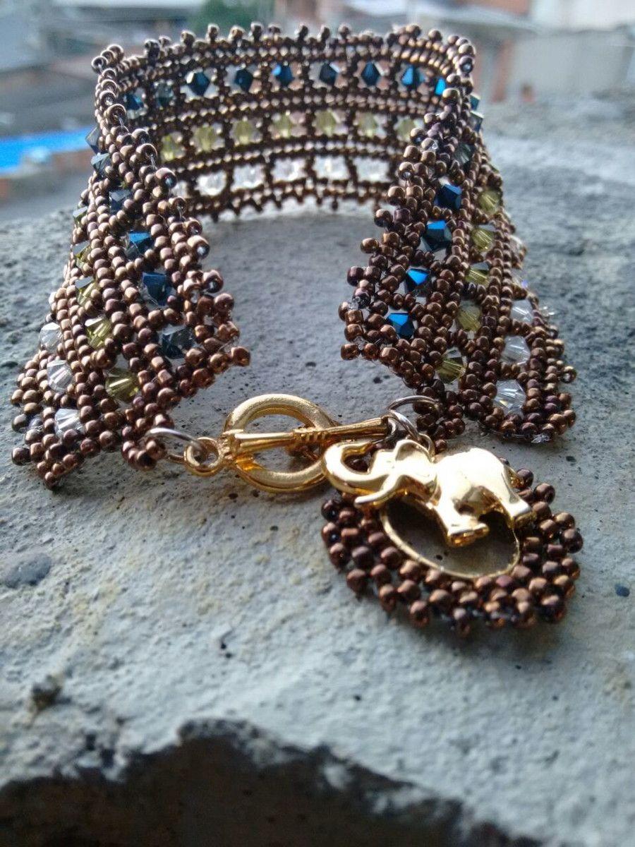 1702b4e3b7a55 Pulseira toda em cristais swarovski e miçangas feita à mão com acabamento  dourado e pingente de elefante.