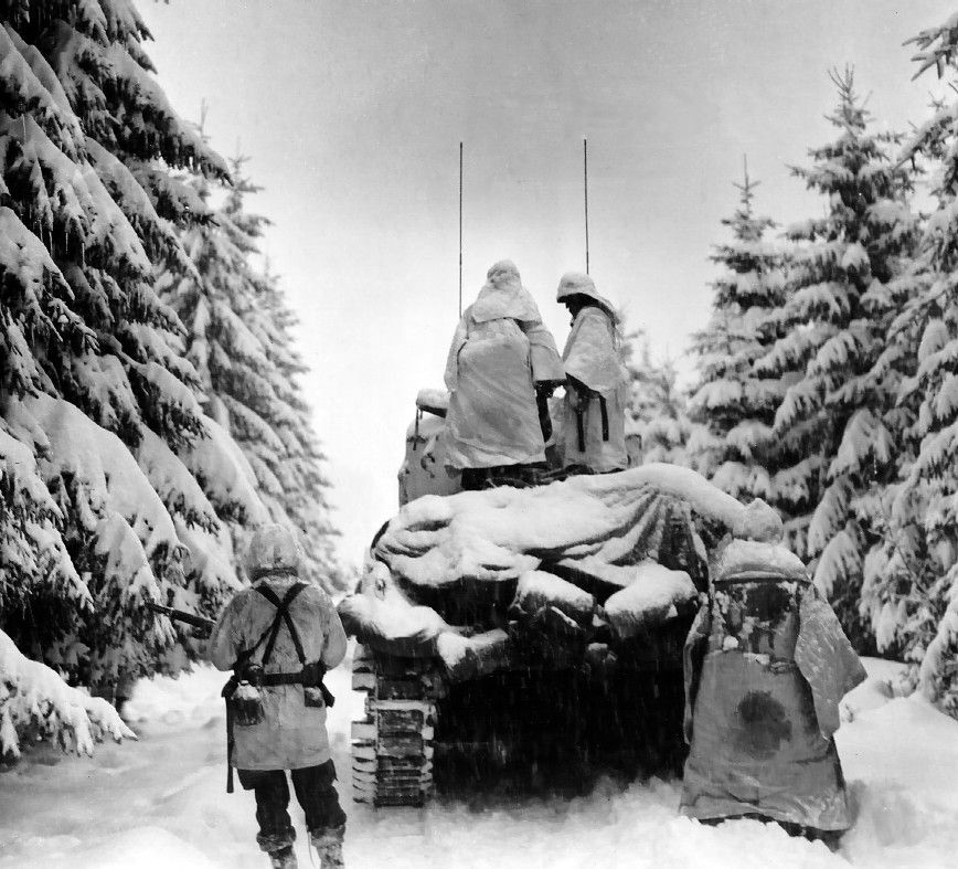 504th Regiment, 82nd Airborne troops advancing through snow-covered forest during the Battle of the Bulge