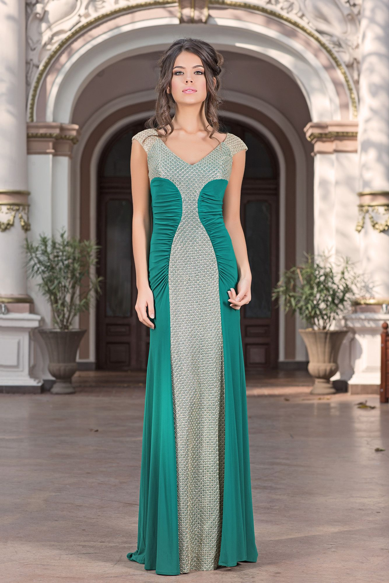 A sleek column gown by Vero Milano. The smooth body of the Adeona gown hugs curves to create a long beautiful look. The v-neck top is embellished with amazing contrasting golden thread that creates a truly lux feel. The back creates a diamond shape, to add a sultry appeal.
