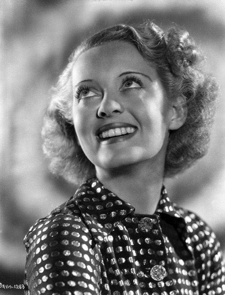 Bette davis portrait smiling and looking up in polka dot black dress