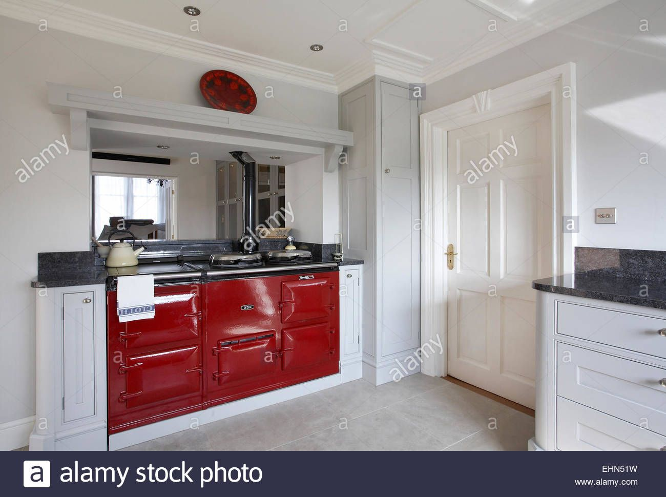 a red aga cooker in a modern kitchen in a home in the uk stock photo