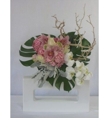 Variegated pink hydrangea, roses, cymbidium orchids, phaleonopsis orchids, manzanita branch and tropical leaves in white ceramic square vase