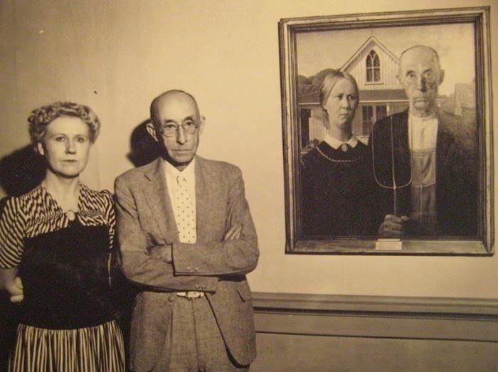 """STRANGE """"AMERICAN GOTHIC"""" COUPLE STAND NEXT TO FAMOUS PAINTING"""