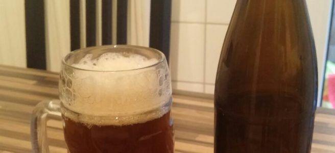 Das welovebier.de- Team zeigt ein Bild, auf dem ein selbstgebrautes Bier zu sehen ist, welches in einen Bierkrug eingeschenkt wurde und daneben die leere Bierflasche steht.
