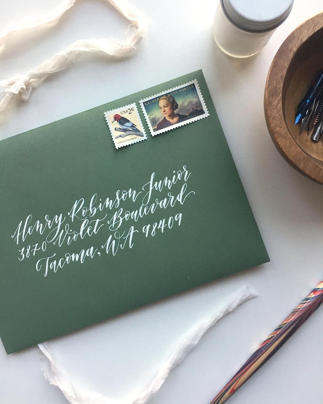 3ac0f2be4378 Envelope calligraphy in our Caroline style for wedding invitations. These  envelopes are a beautiful mid-green with white addressing