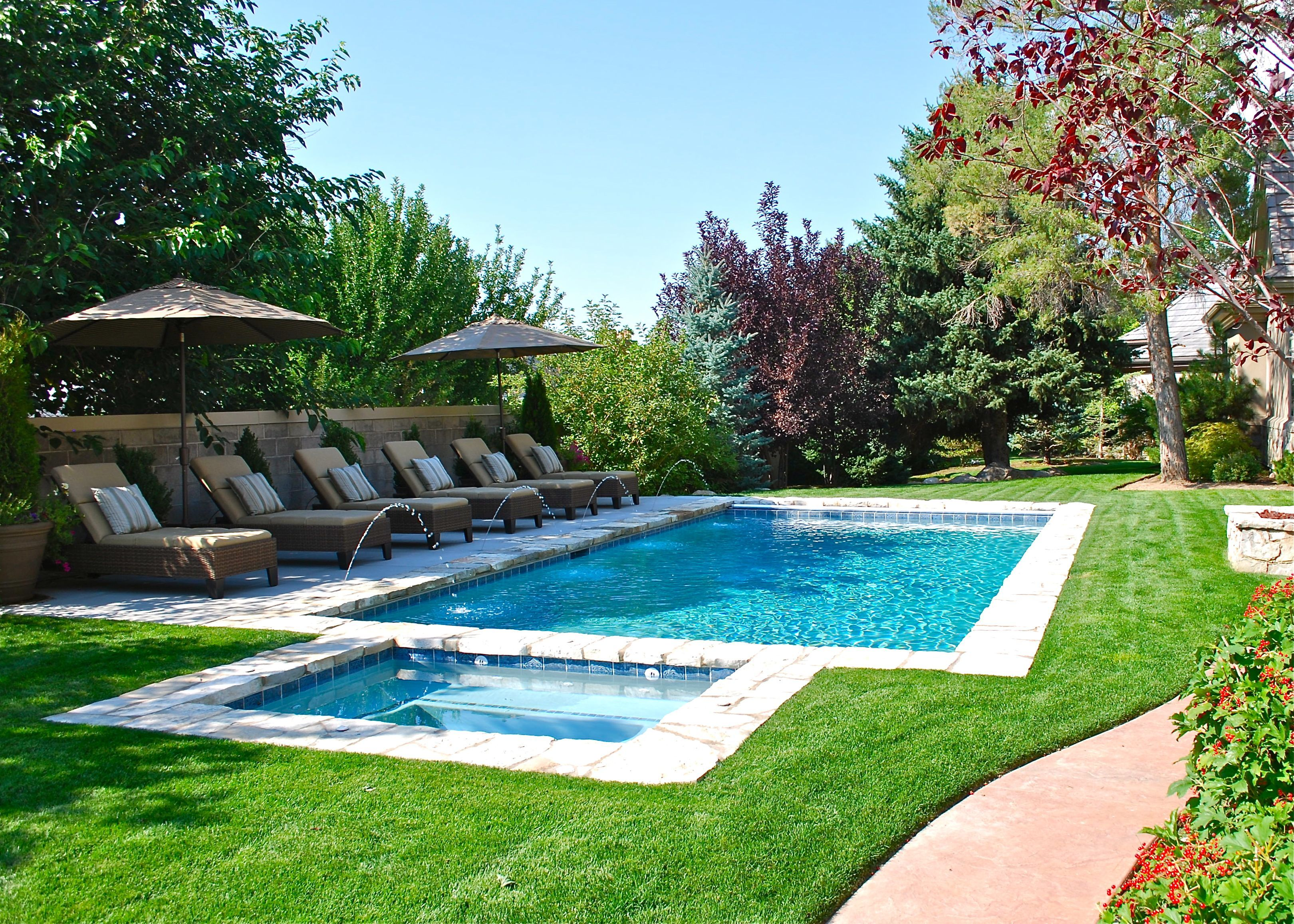 Backyard swimming pool with minimal decking deckjets and for Pool landscape design ideas