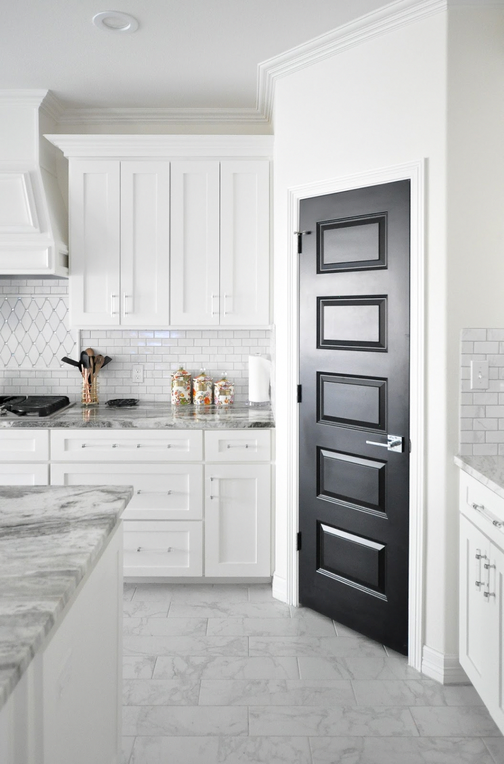 A Black Pantry Door In An All White Shaker Cabinet Kitchen With Marble Floors And Backsp Kitchen Remodel Inspiration Kitchen Remodel Small White Shaker Kitchen