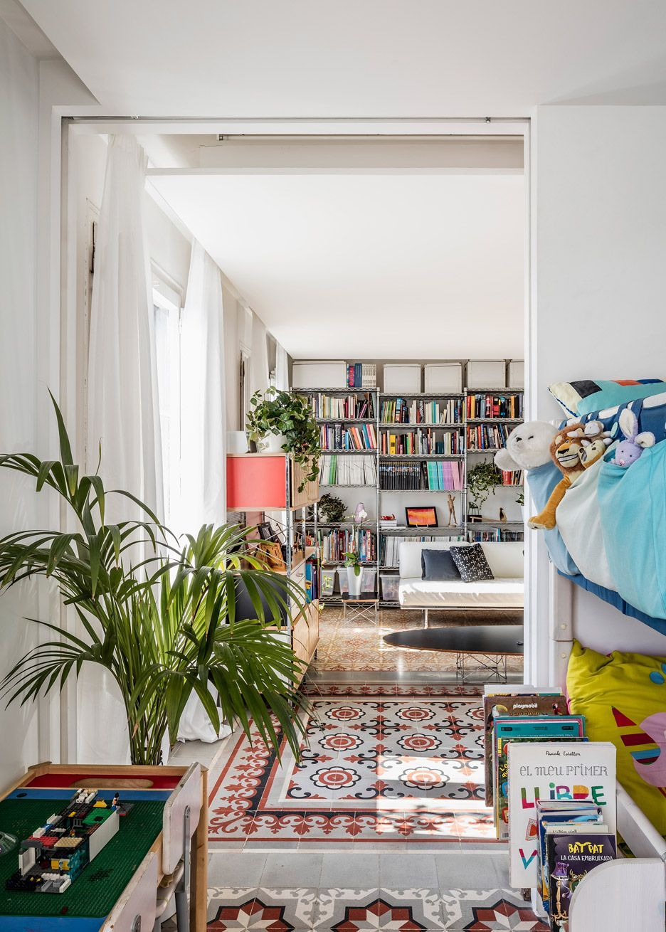 Living Room With Potted Palm Tiled Floors Bookcases And Beige Couch