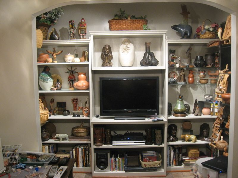 Pottery, sculpture, basketry and books adorn the shelving in this side TV Den