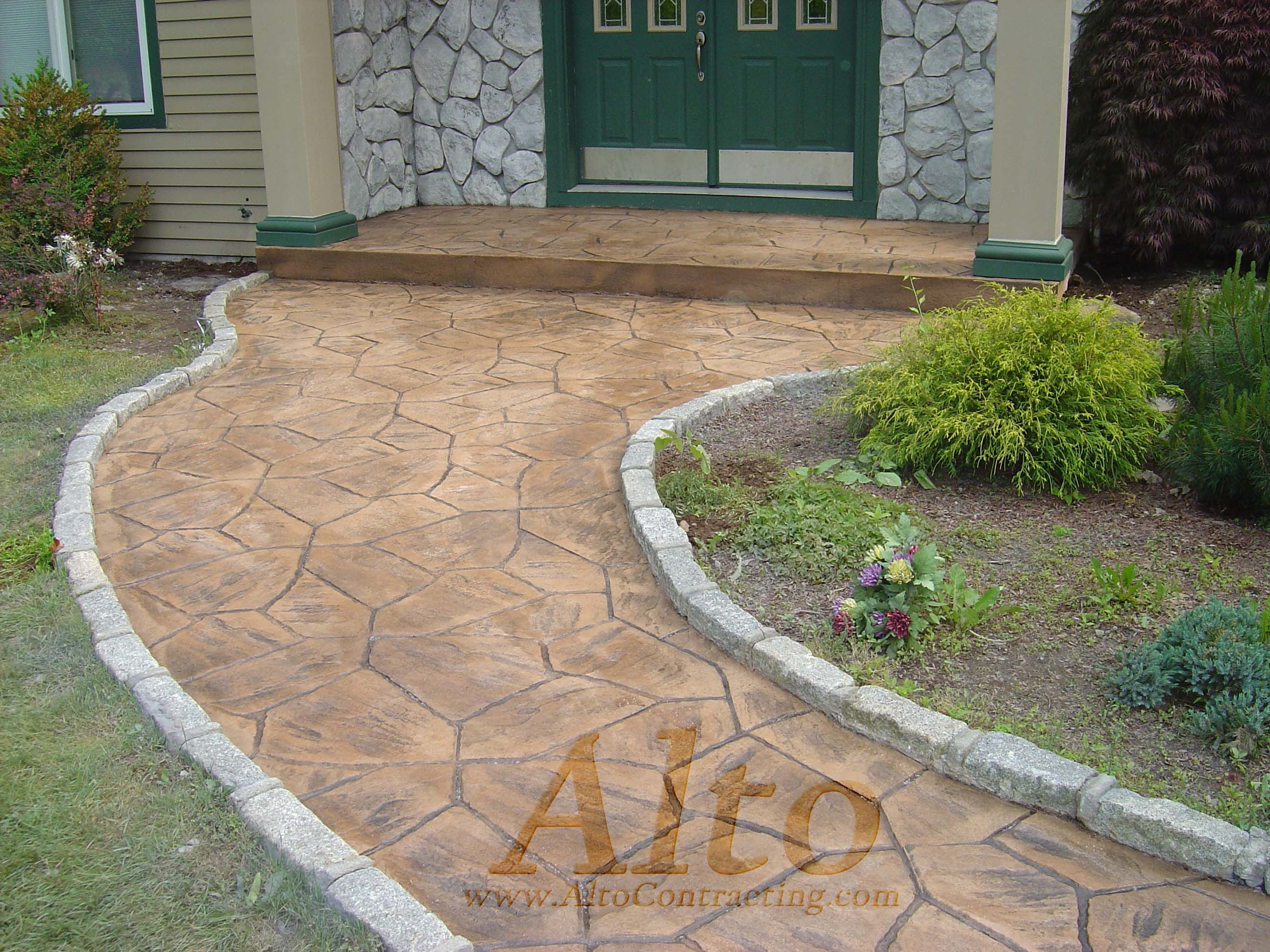 Stamped concrete walkway with cobblestone curbing.