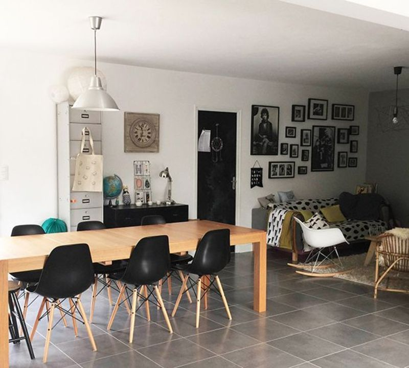 salle a manger avec grande table bois et chaises eames noires coin salon sol en carrelage gris. Black Bedroom Furniture Sets. Home Design Ideas