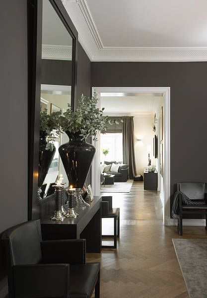 Dark walls highlights as well the classical stucco and moldings in this stunning apartment in Frogner.