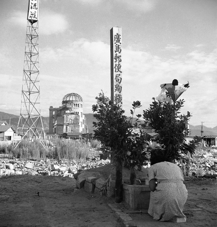 An atomic bomb survivor prays at the Hiroshima Post Office
