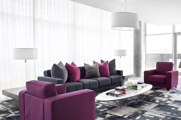 Living room design in grey and purple colors and a lot of cushions