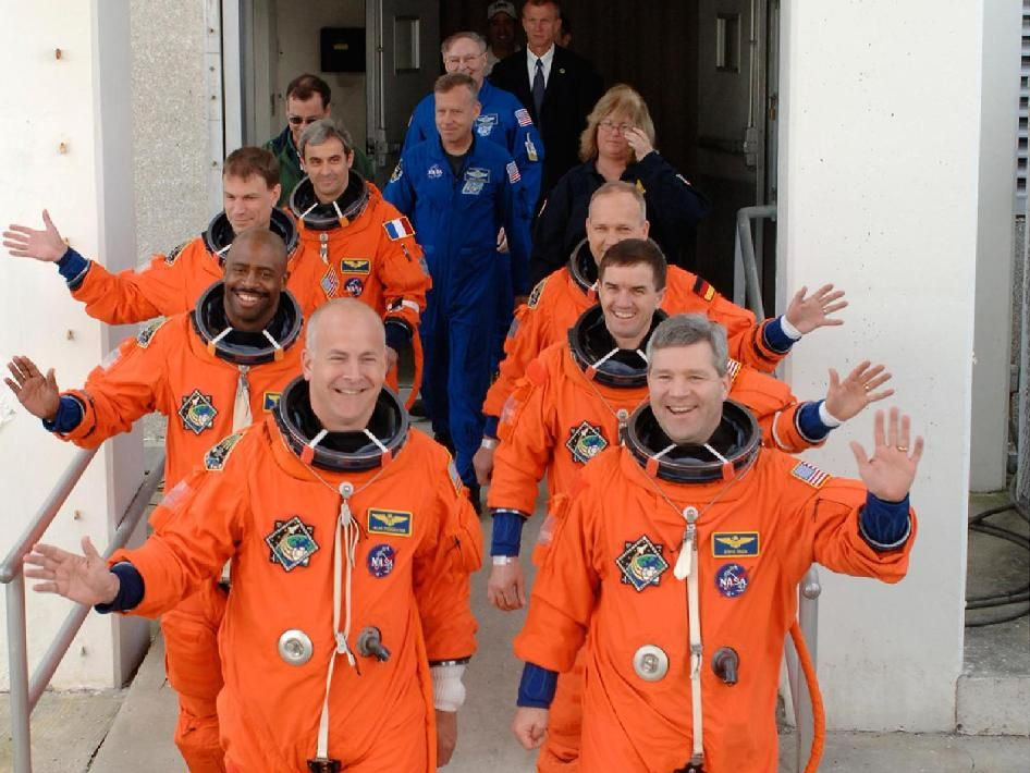 In this image from December 2008, the STS-122 mission crew members stride out of the Operations and Checkout Building, eager to ride to the launch pad and take their seats in space shuttle Atlantis. On the left, front to back, are Alan Poindexter, followed by Leland Melvin, Stanley Love and Leopold Eyharts. On the right, front to back, are Commander Steve Frick, followed by Rex Walheim and Hans Schlegel. Schlegel and Eyharts represent the European Space Agency. Poindexter died on Sunday…