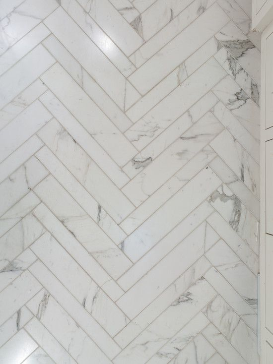 b57341e001 Detail shot of flooring of a beautifully understated bathroom with white  carara marble and accents in a herringbone pattern. The feeling is  luxurious
