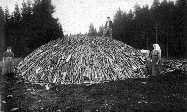 Wood pile before covering it with turf or soil, and firing it (around 1890)