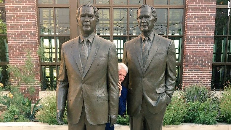 A viral photo shows Bill Clinton peeking out between the statues of George H.W. Bush and George W. Bush with a sly grin on his face.