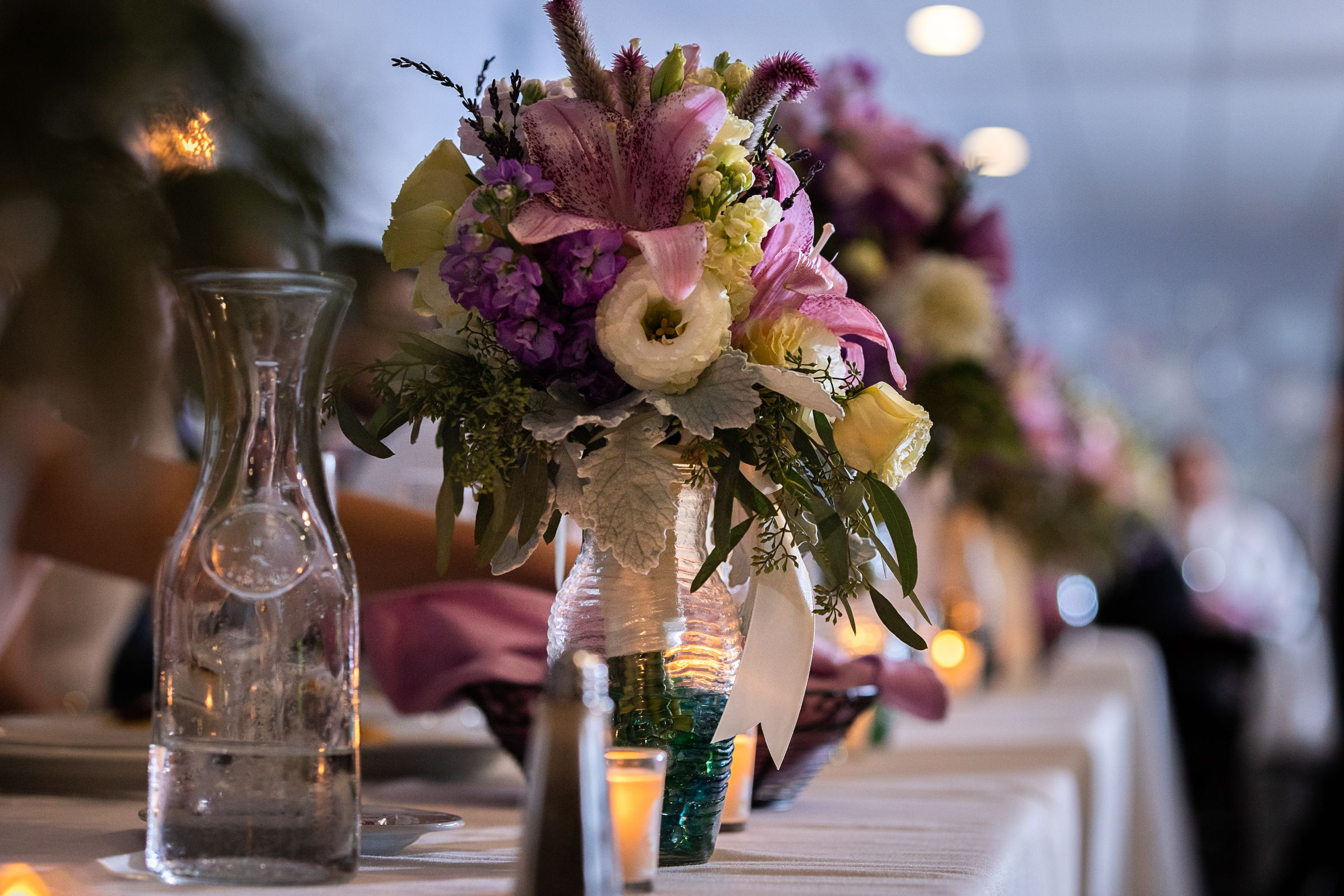 The ceremony was beautiful, now it's time to party.  The  bouquets are too pretty to toss aside, use them on your head table!  A lot of venues even have vases you can use for FREE to display your bouquets.    #headtabledecor #weddingflowers #bridesmaidflowers #bridesflowers #chicagomichiganwedding #swmichiganweddingvenue #flowers #tabledecor #purpleflowers #purpleyellowwhitebouquets
