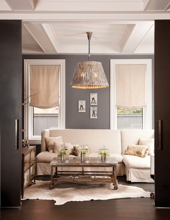 Love The Dark Grey Wall Color Slipcovered Sofa Pendant Light And Cowhide Rug Living Room Grey Interior Home