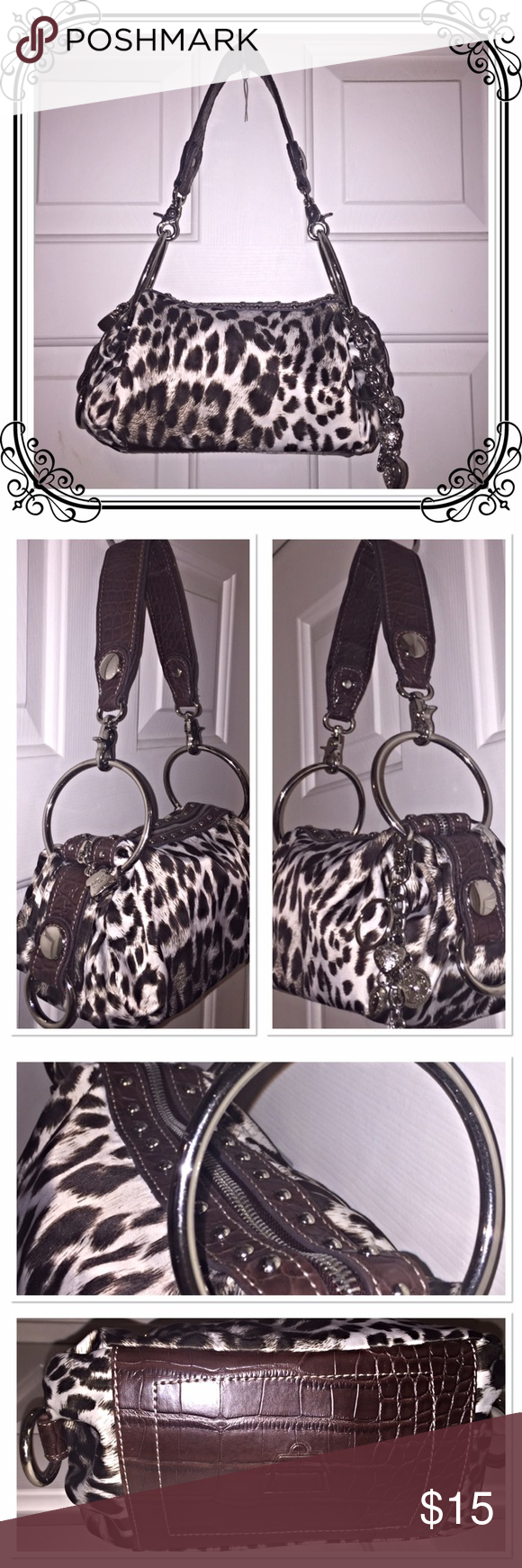 Kathy Van Zeeland Shoulder Purse Cheeta print in brown and white. Top-zip closure decorated with silver circle studs and a lock charm. O-ring detail hardware and key fob with hearts is removable.  An inner zipper pocket and two slip-in pockets.  A few pen-ink stains in one corner.  In very good conditions❣️ Kathy Van Zeeland Bags Shoulder Bags