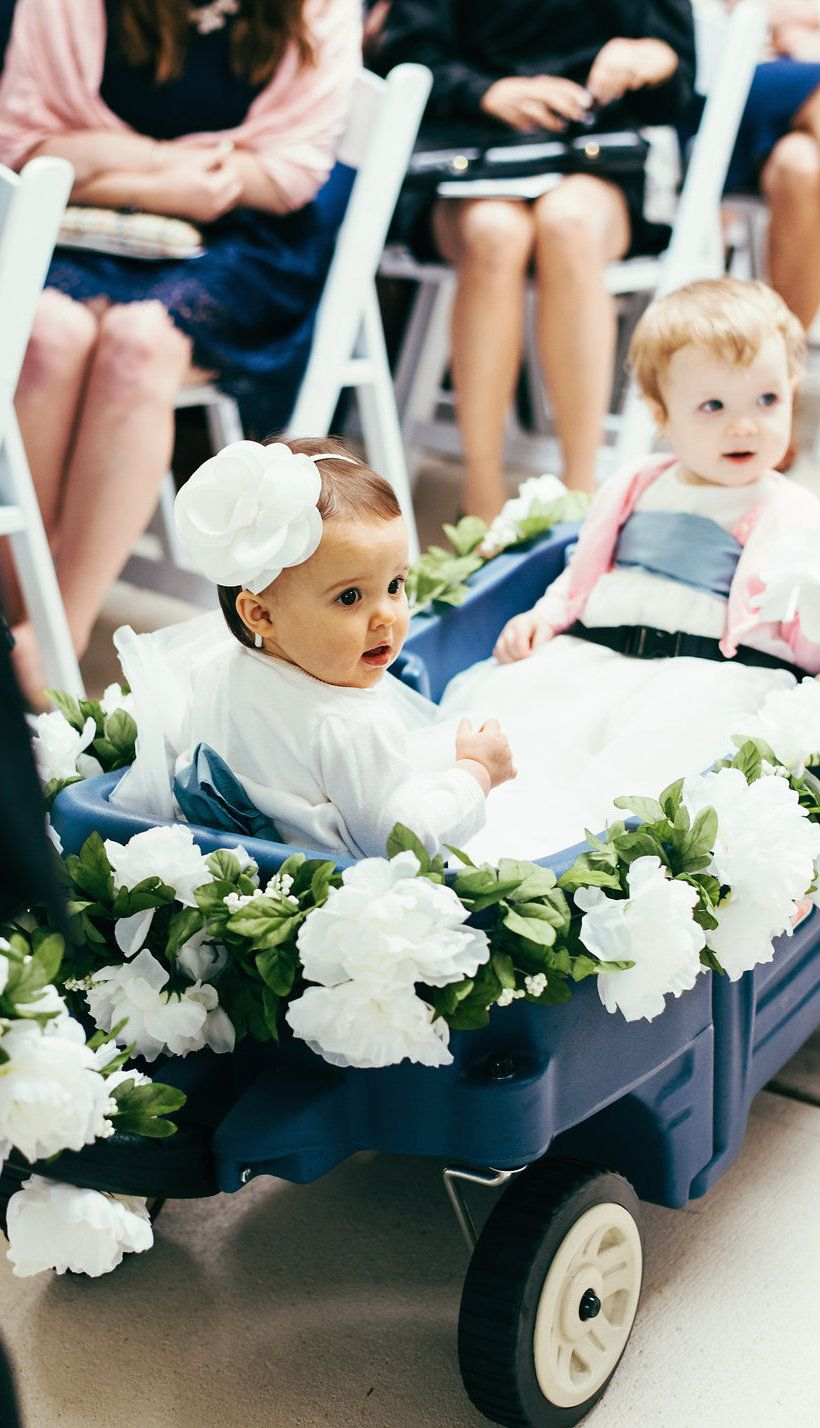 I attached a faux floral garland to the baby flower girl wagon HOW