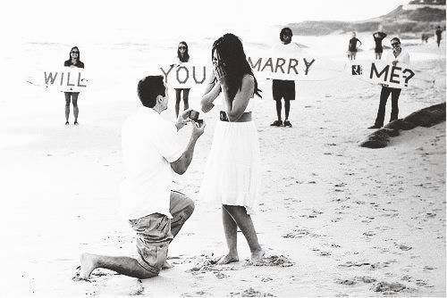 """Have family members hold up signs asking, """"Will You Marry Me?"""""""