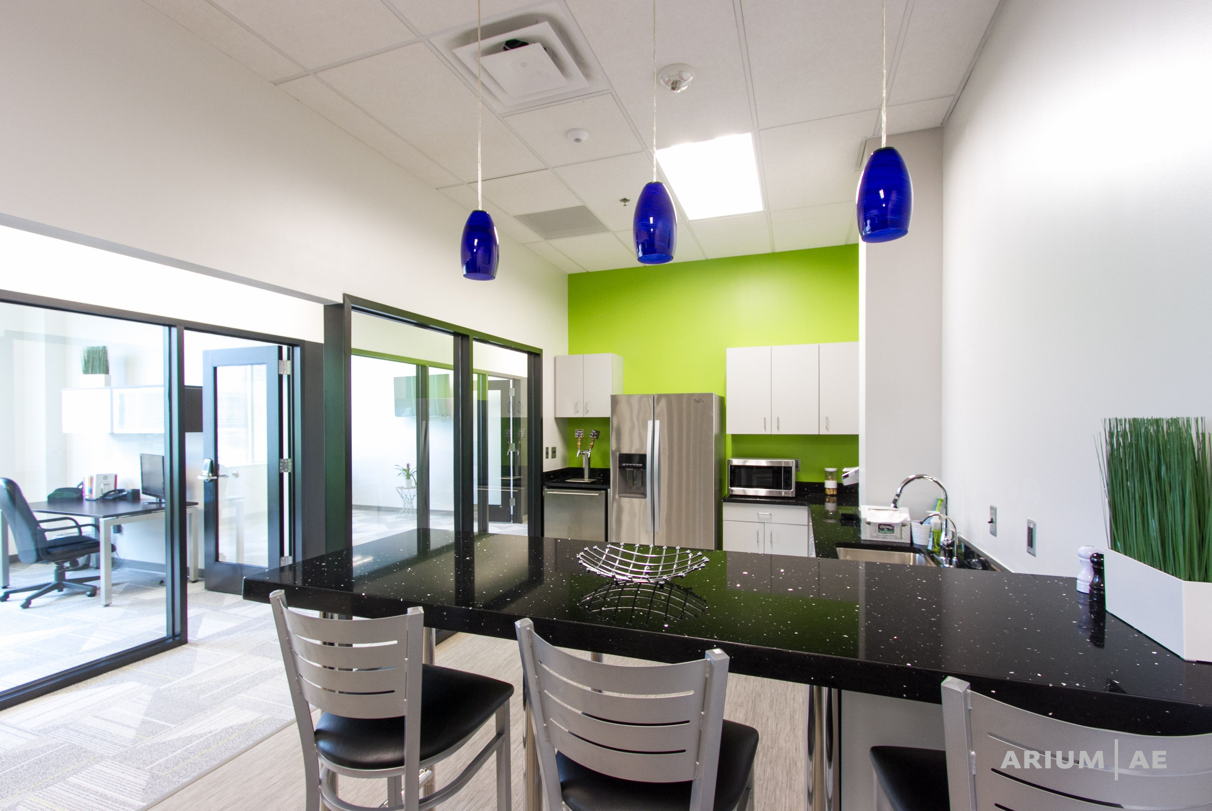 Break Area With Green Backsplash, Blue Pendant Lights, Black Stone  Countertops, And Black Framed Glass Walls