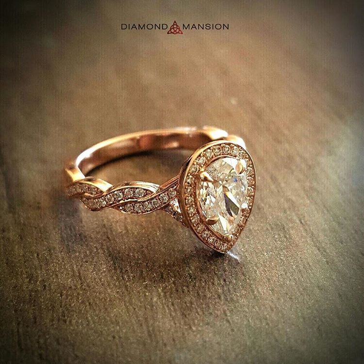 An Elegant Pear Shaped Diamond Sits In A Rose Gold Setting With