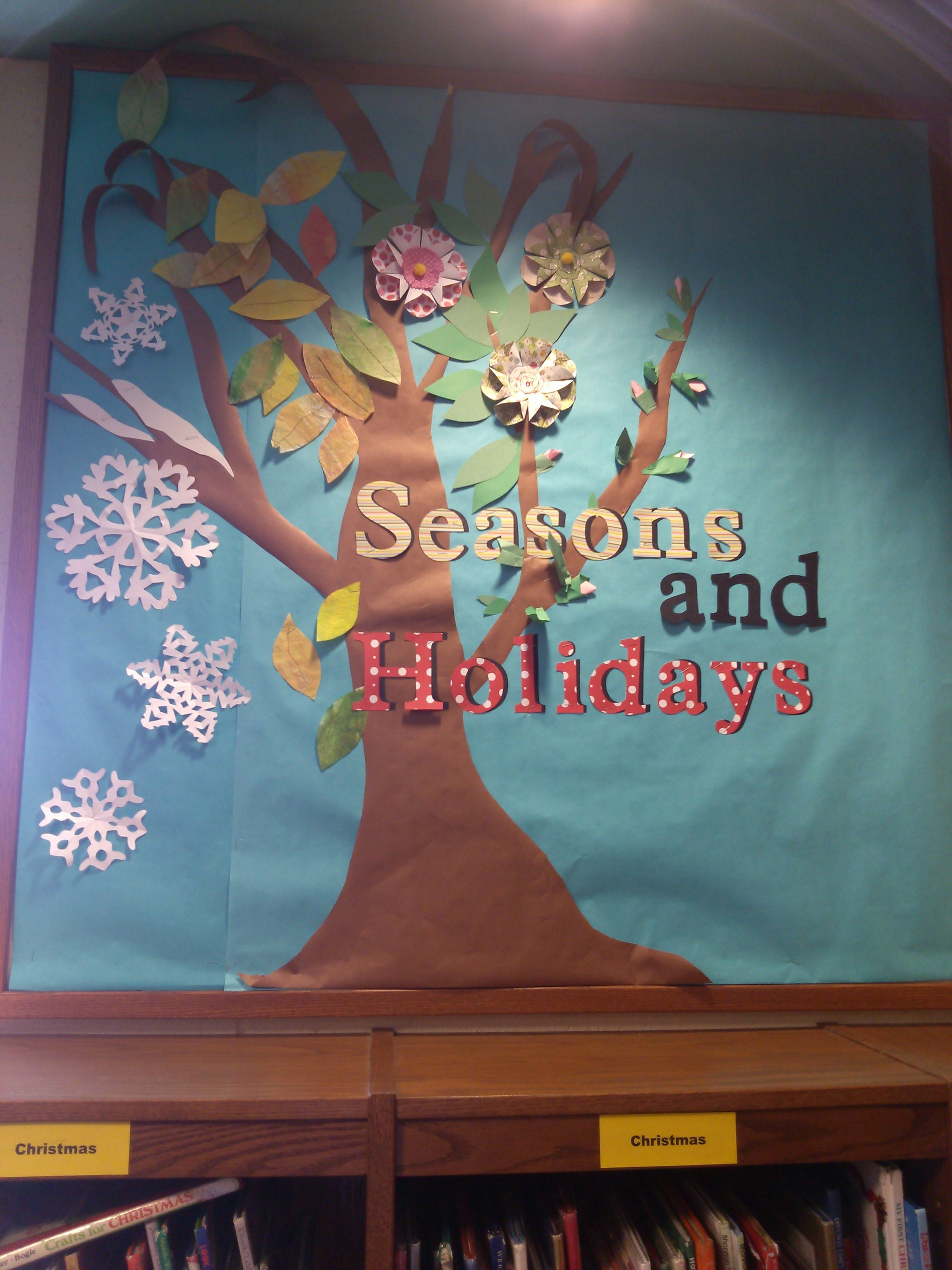 bulletin board in elementary library with all seasonal and holiday books below