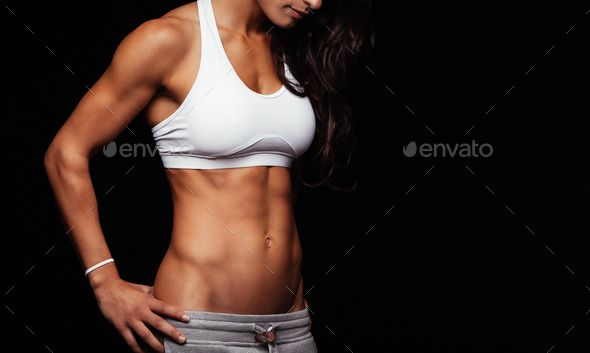 Sporty model with perfect abs by jacoblund. Fitness female model torso with her hands on hips. Femal...