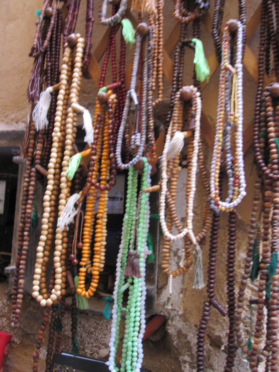 """One shop displayed hundreds of prayer beads on its three walls—ivory and amber, lapis and coral, sandalwood and ebony."""