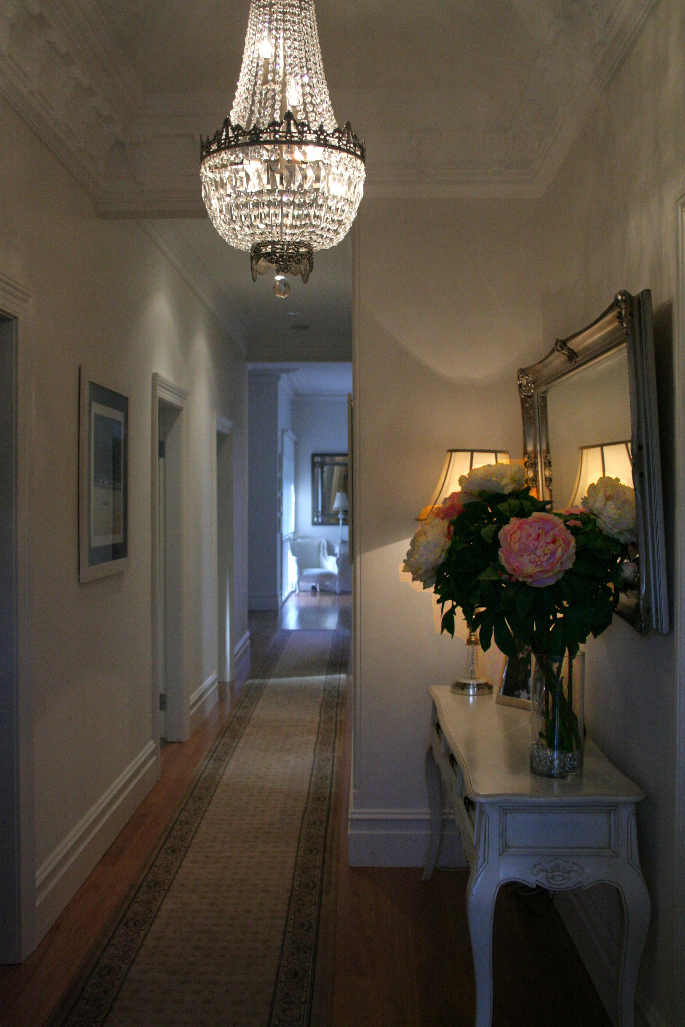Traditional style chandelier brings glamour to a hallway
