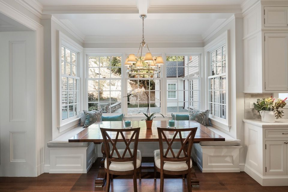 The breakfast room is warm and inviting with large cottage double-hung windows and banquette seating that looks to the backyard.