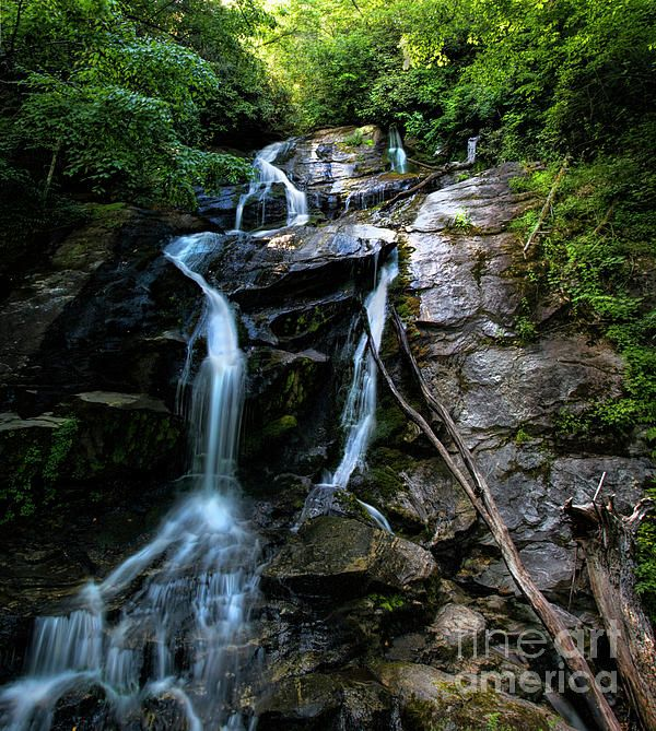 Ammon Creek Falls trickles down the grand rock ledge warmly lit by the afternoon sun.