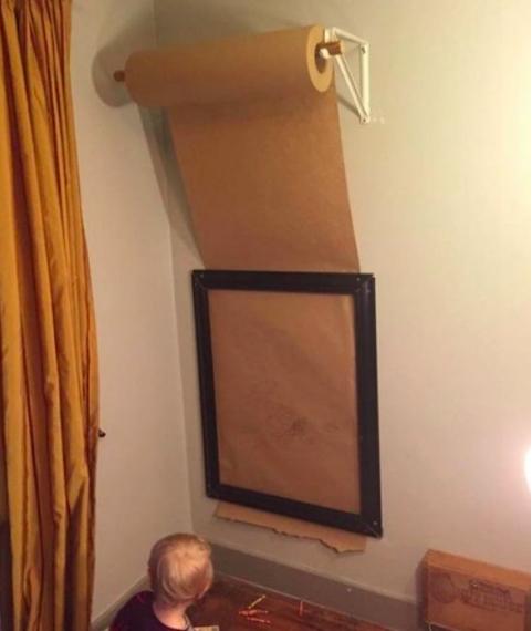 Befestige eine Rolle Packpapier über einem Rahmen, damit dein Kind jeden Tag ein neues Meisterwerk erschaffen kann.