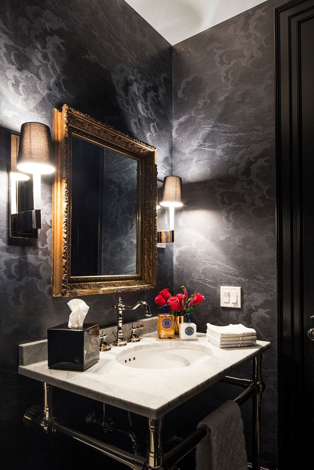 The powder room features a white sink counter surrounded by elegant black walls lighted by a couple of wall lights photo credit erik rotter