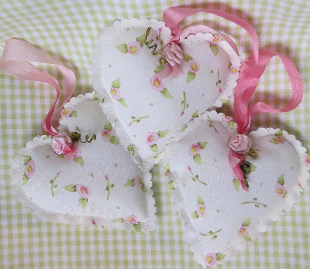 These three matching sachets are meant to loop over a clothes hanger to add a lily~of~the~valley scent to your closet. Made from a lovely floral cotton fabric on the front and back, the loop is a variegated pink silk ribbon to pick up the color of roses in the fabric. I have added a sweet little faux pink flower and stem to finish off the 4 x 4 heart. Poly batting which is infused with lily~of~the~valley essential oil is stuffed into the hearts and the edges are scalloped.  This would make a…