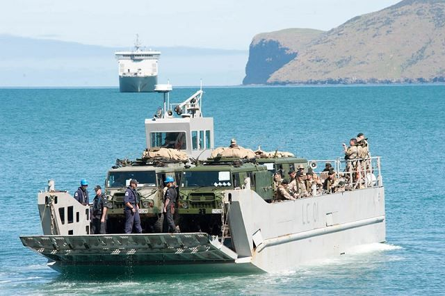 Soldiers practice amphibious landing at Akaroa Harbour New Zealand prior to start of exercise in Timaru. HMNZS Canterbury is in the background and the trucks on board are Pinzgauers. Photo courtesy of New Zealand Defence Force Public Affairs.