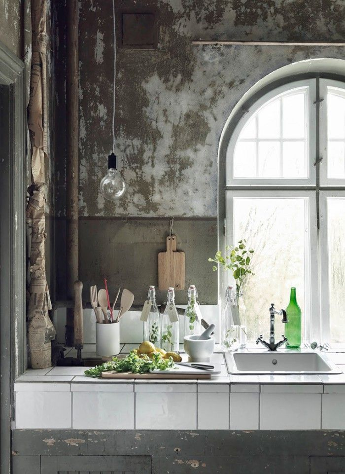 Keuken met witte tegels als werkblad en een betonnen achterwand ...