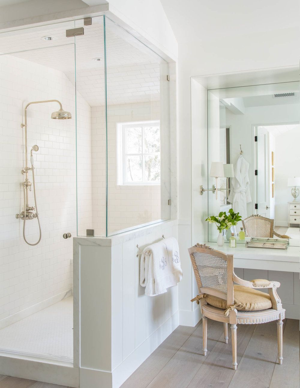 Crisp and bright white bathroom with glass shower and gold hardware ...
