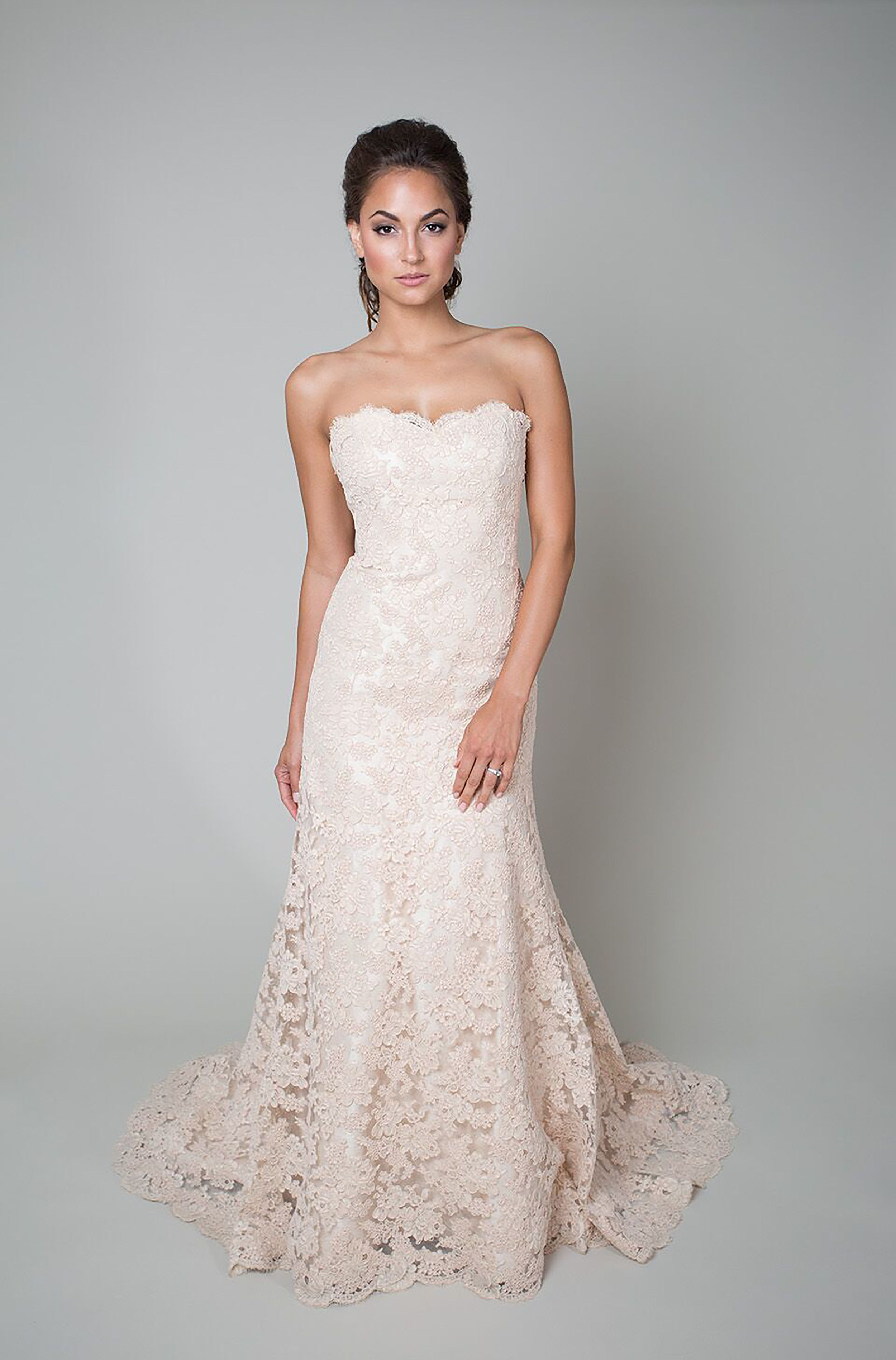 Wedding dress with bow on back  This trumpet style wedding gown features a blush base with blush