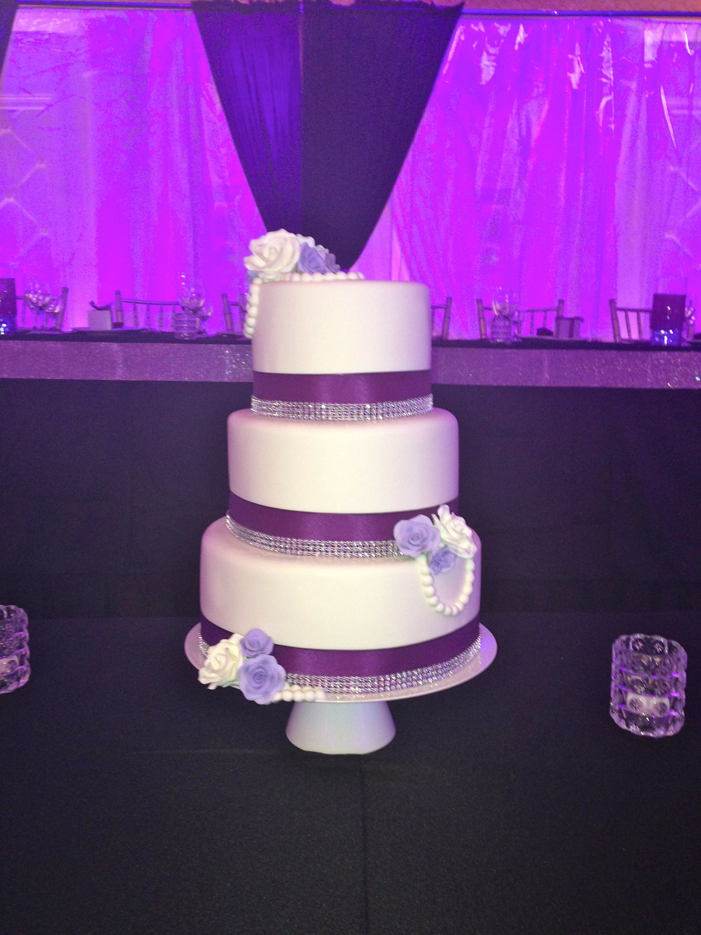 Pretty Purple Ribbon And Silver Rhinestone Bling Surrounds Each Tier Of This White Wedding Cake