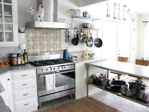 Many people love the country-cottage kitchen style. This is a beautiful example with the white cabinets, crafty tile, and enticing details like the rooster statue and the work table doubling as both storage and eating space. Visit homecraftsdiy.com