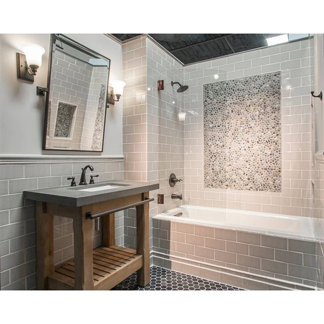Taupe Subway Tile And Pebble Mosaic Accents, Paired With An Industrial Vanity And Oil Rubbed